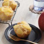 米粉で作ったりんごのマフィンが青いお皿に一つのっている。そばにりんごが2つある。