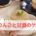 小さなケーキが白いお皿にのっていて、フォークが添えられている、近くに姫りんごが飾ってある。