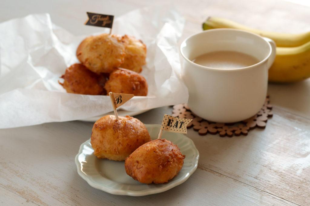 バナナのドーナツが2個水色のお皿にのっていて、ピッグが刺さっている。近くに白いマグカップに入った甘酒が添えられている。