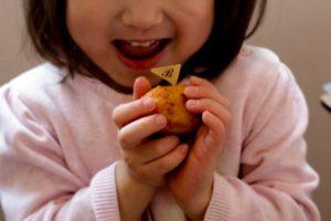 バナナドーナツ1つ持っている女の子が微笑んでいる