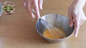 ボウルに卵入って、泡だて器で混ぜている
