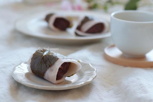 桜もちが白いお皿にのって近くにお茶がおいてある。